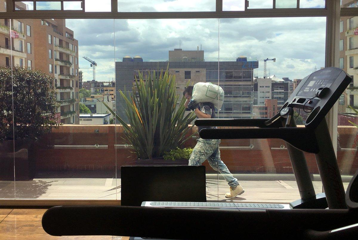 Un lavoratore passa di fronte alle vetrine di una palestra, a Bogotà (Colombia)