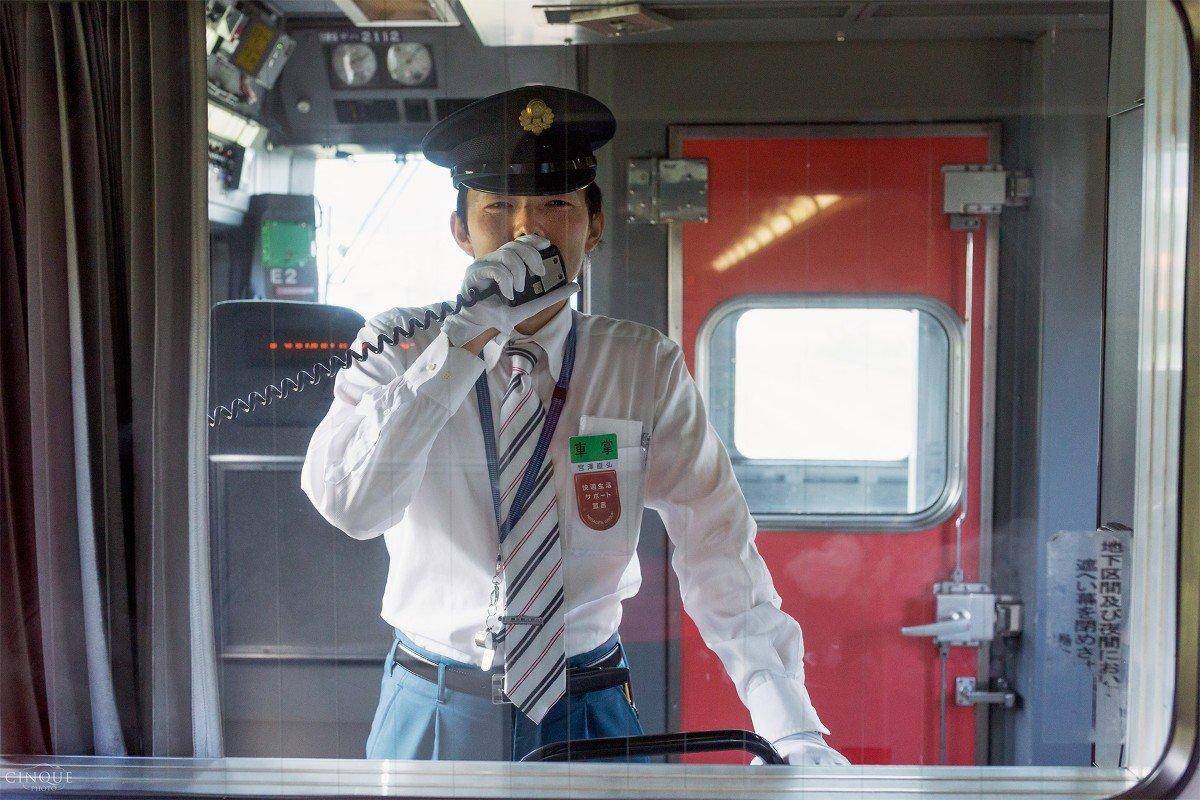 Un capotreno esegue gli annunci sulla tratta ferroviaria di Osaka, Giappone. Japan Rail Pass