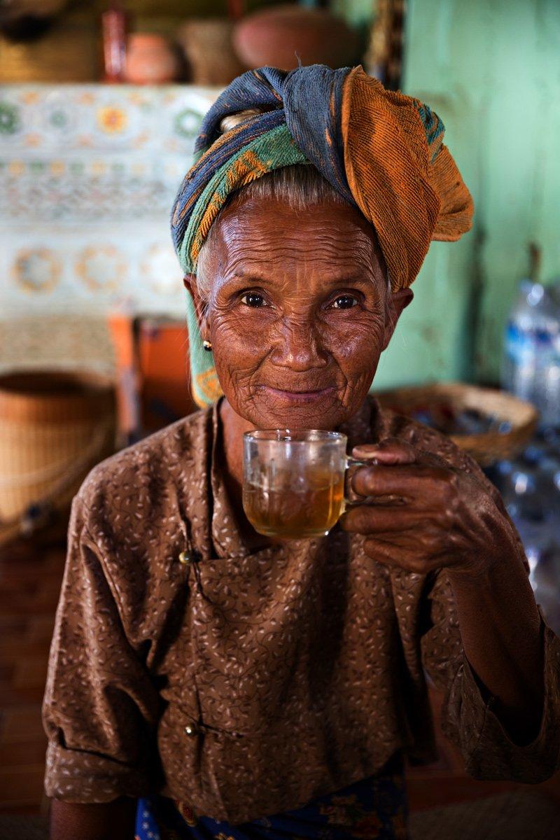 Una amabile nonnina sorseggia the in un tempio buddista