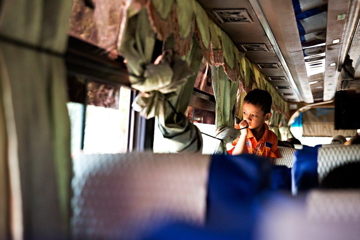 Su uno degli autobus più economici, un bambino osserva fuori dai finestrini