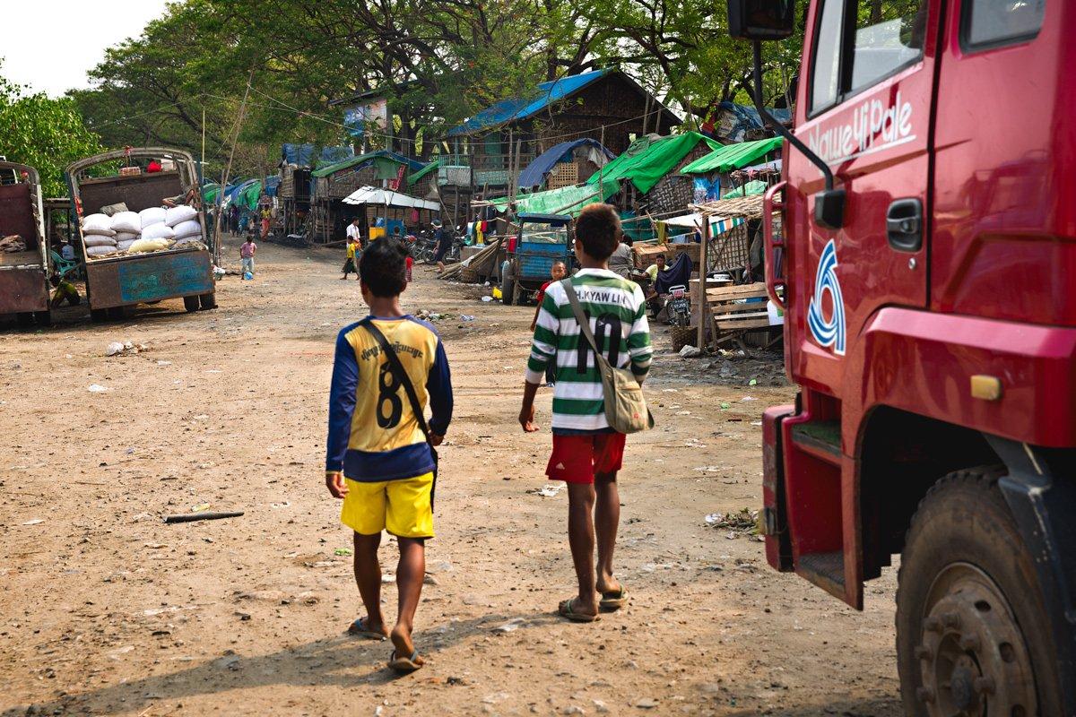 Mandalay, due bambini percorrono la strada di sabbia e terra costeggiando il molo