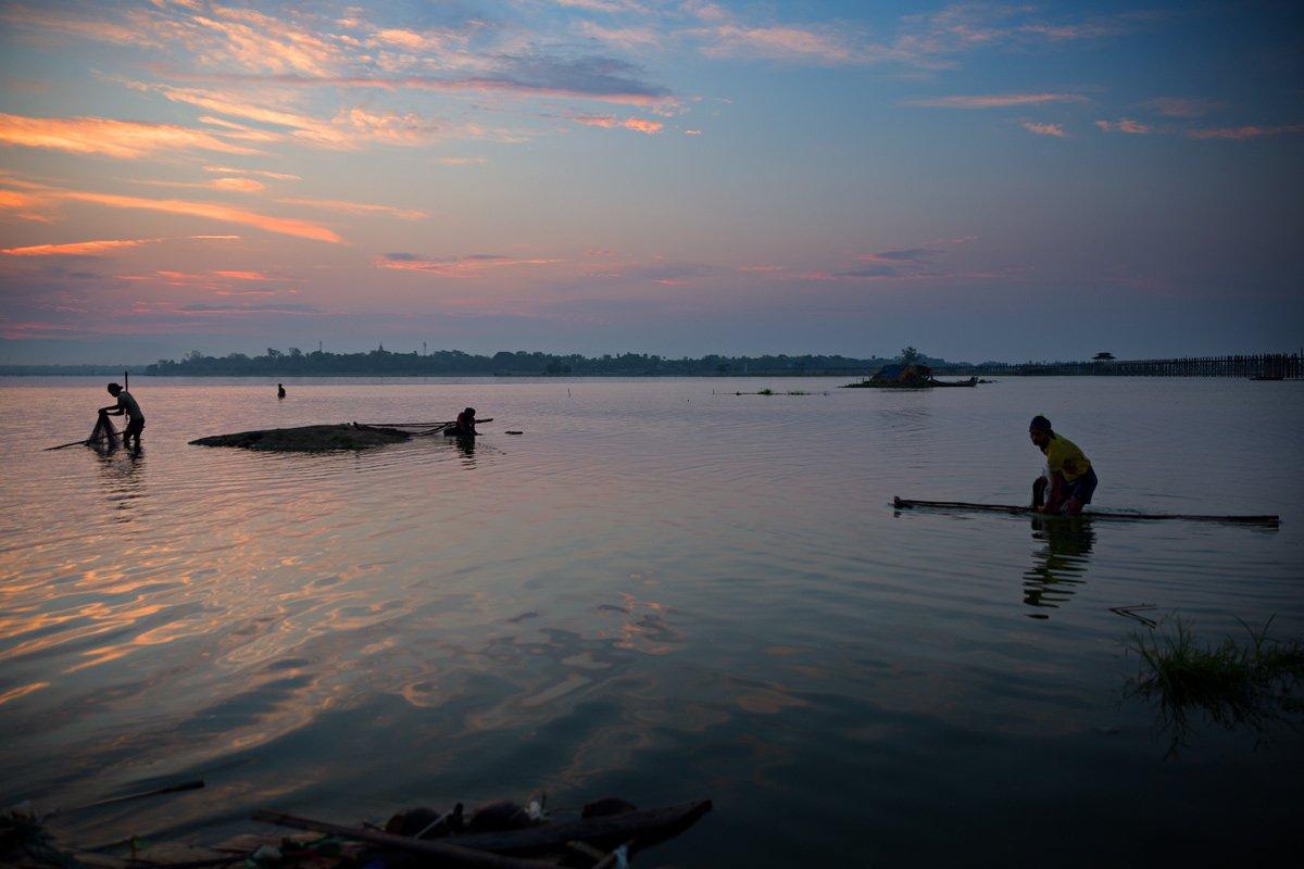 I pescatori immersi nelle acque torbide fino al bacino gettano le proprie reti