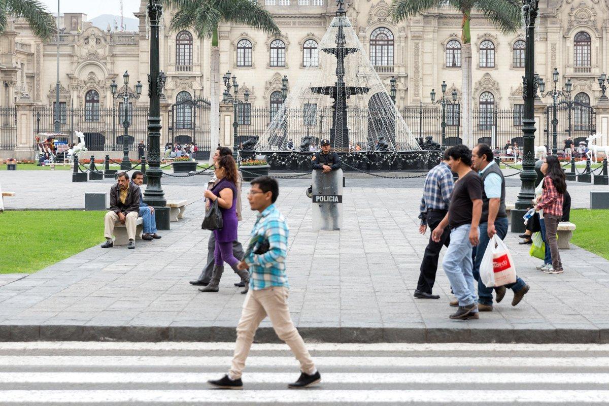 Un uomo sorveglia i passanti di Plaza de Armas, Lima (Perù)