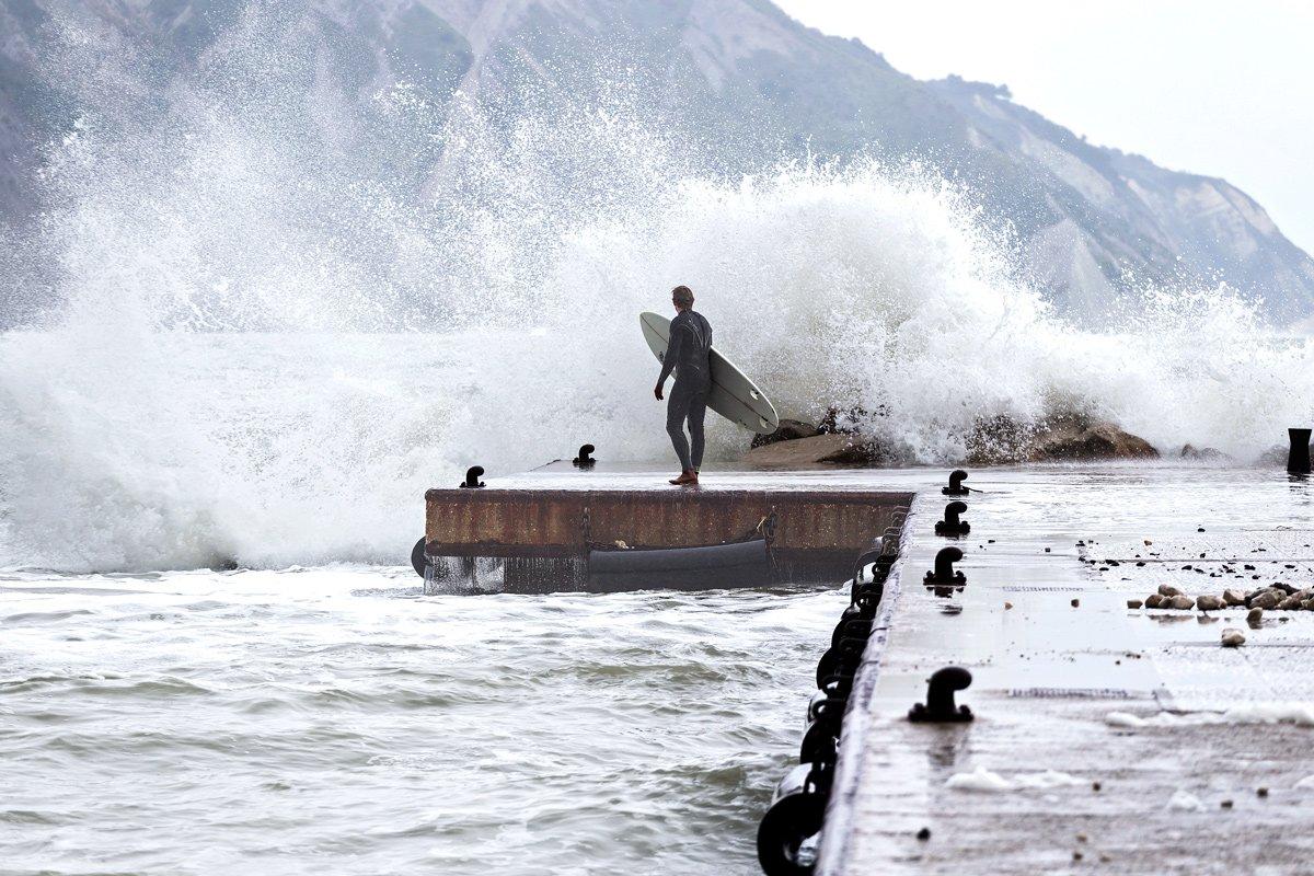 Un surfista valuta le onde, riviera del Conero (Italia)